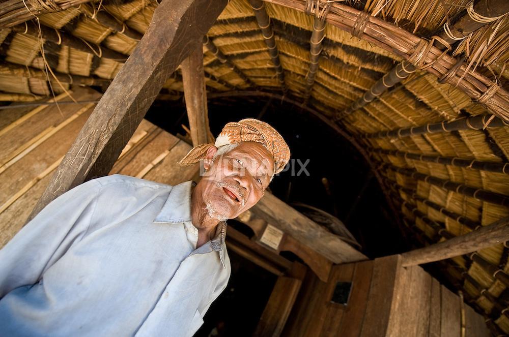 Old man at entrance to traditional Manggarai home, Wae Rebo village, Flores.