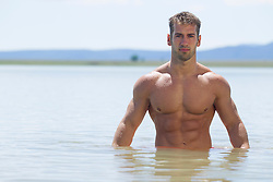 muscular shirtless man standing in a lake in New Mexico