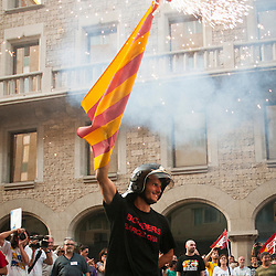 A firefighter carries a Catalan flag with fireworks attached to the top in protest of the increased sales tax.