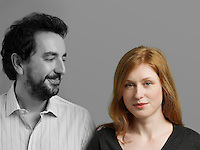 Portrait of beautiful mid-adult woman with man looking at her against gray background