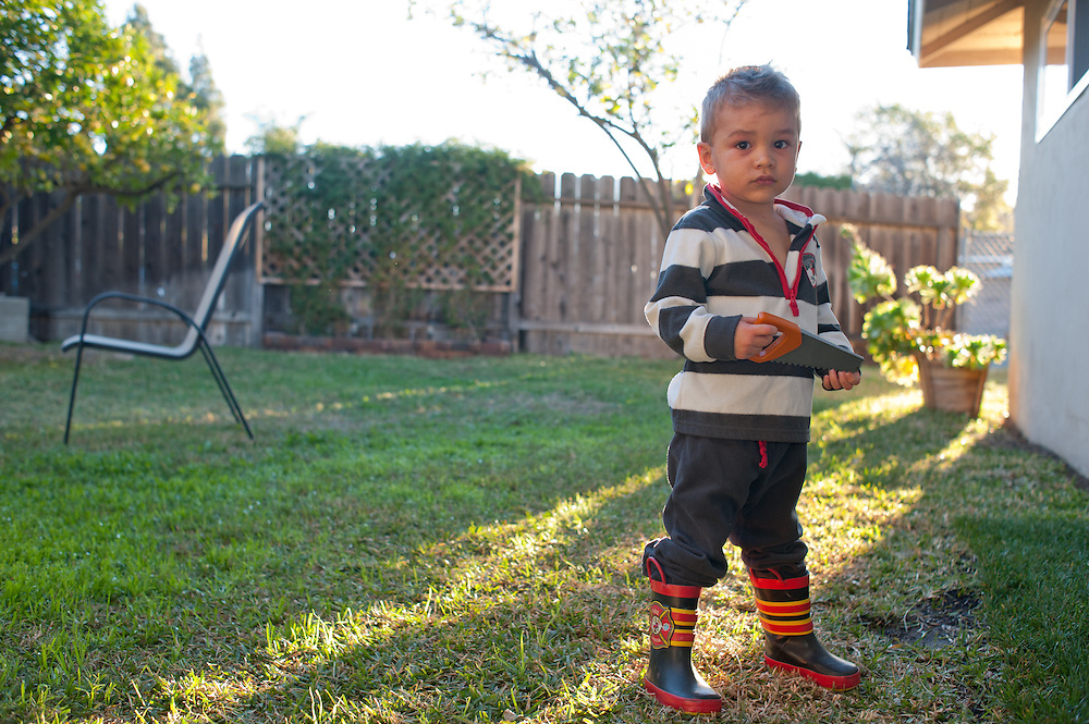 young boy proudly showing off new rubber fireman's boots on lawn