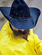 A cowboy moves stock behind the scenes at the rainy Parada del Sol Rodeo in Scottsdale, Arizona, February 12, 2005...