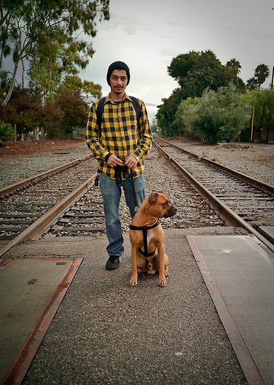 Man with his dog by the railroad track.