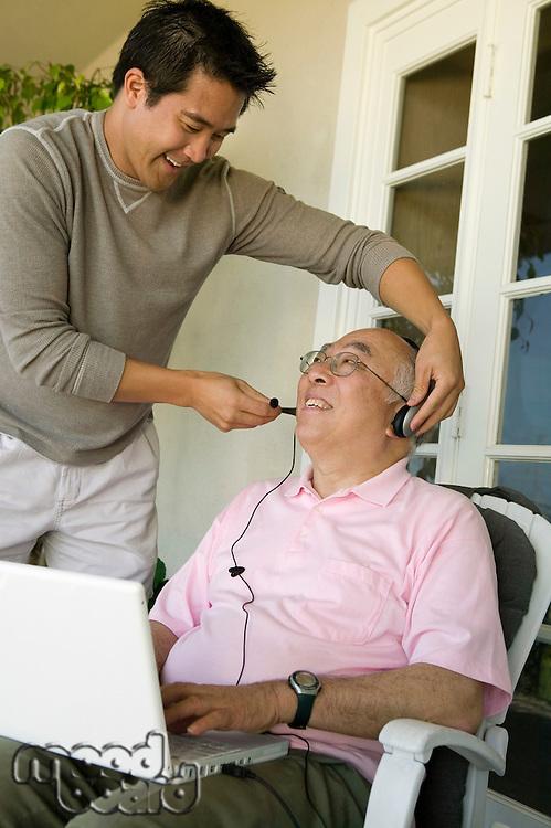 Son Adjusting Headphones on Father