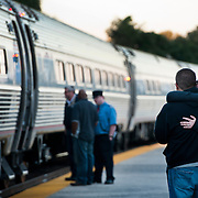 Julia and Jaysn Schaener embrace at the Kemper Street Station after Julia's parents and brother from Germany boarded the Northeast Regional line heading to Washington DC.  The couple wed one week earlier and may not see Julia's parents again for another year. <br /> <br /> This year the photography department took on a monthly photo page for which we photographed, well, whatever we wanted.  I have always been drawn to the train station here in Lynchburg.  With its timeless feel, the past seems to come back to life in our station that opened in 1912.  The morning of my deadline, I came across this couple lost in their embrace. I was happy to find a quiet moment in the busyness of the morning commute.
