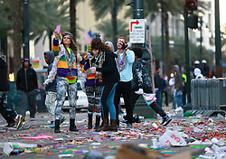 17 Feb 2015. New Orleans, Louisiana.<br /> Fat Tuesday. Mardi Gras Day. Tourists in the trash take selfies on Canal Street after the parades have passed.<br /> Photo; Charlie Varley/varleypix.com