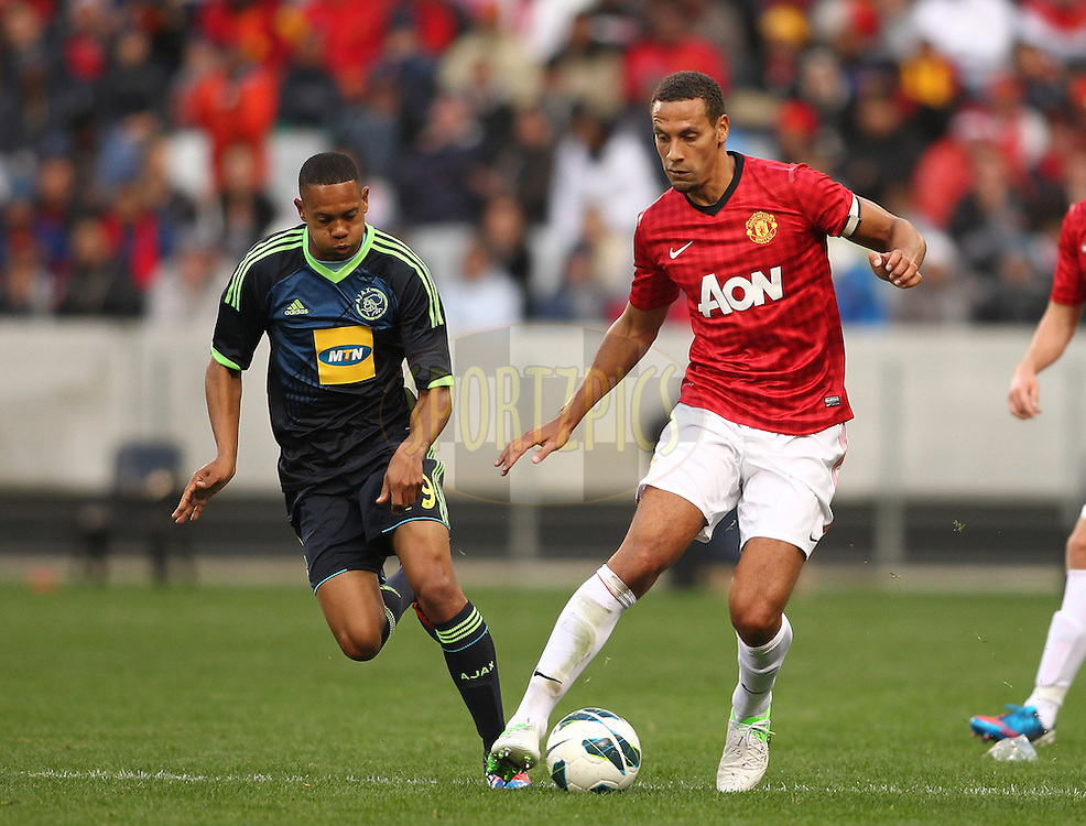 Manchester United captain Rio Ferdinand attempts to get away from Brent Carelse of Ajax Cape Town during the Football Invitational 2012 match between Ajax Cape Town and Manchester United held at Cape Town Stadium on 21 July 2012 in Cape Town, South Africa..Photo by Shaun Roy / Sportzpics