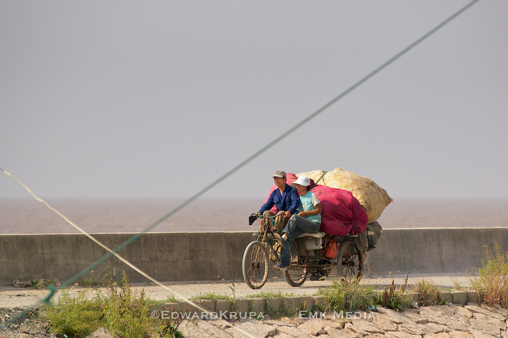 A couple travelling on a motorized tricycle by the South China Sea near Wenzhou China 2009.
