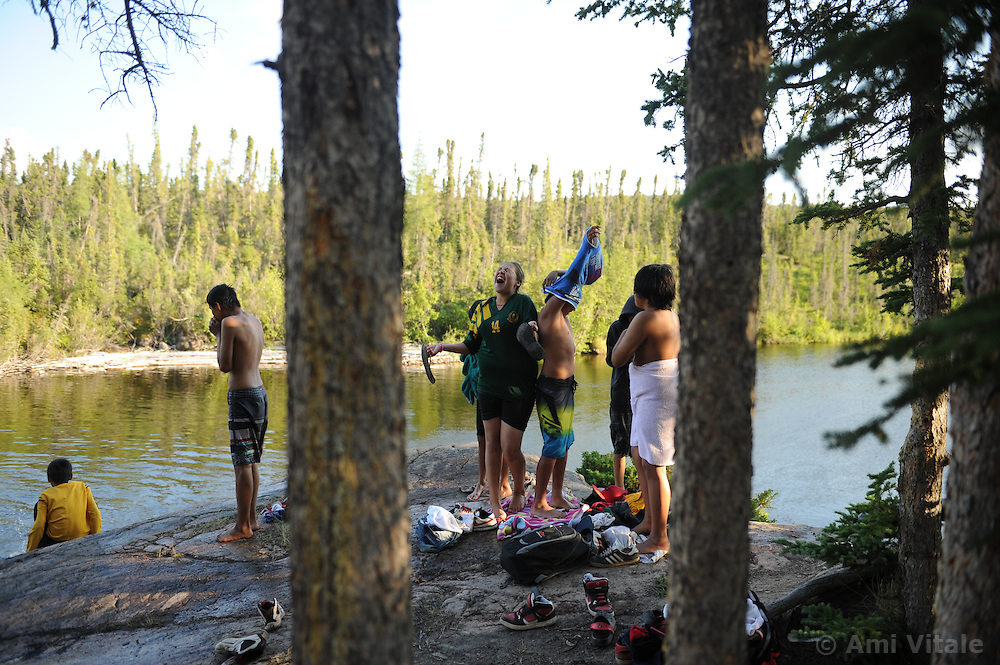 """First Nation Dene youth gather  during a spiritual gethering in Reliance after a group returns on a canoe trip from the Upper Thelon River is """"the place where God began.""""  Sparsely populated, today few make it into the Thelon. Distances are simply too far, modern vehicles too expensive and unreliable. For the Dene youth, faced with the pressures of a western world, the ties that bind the people and their way of life to the land are even more tenuous. Every impending mine, road, and dam construction threatens to sever these connections. In July and August, 2011 a group of youth paddled to their ancestral hunting ground and spiritual abode.  this next generation of young leaders will be the ones who will need to speak for the Thelon the loudest. (Photo by Ami Vitale)"""