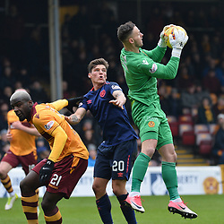 Motherwell goalkeeper Trevor Carson saves from Ross Callachan (Hearts) watched by Cedric Kipre (Motherwell) during the Scottish Cup quarter final between Motherwell and Hearts at Fir Park, where the home side made it into the semi final draw with a win.<br /> <br /> (c) Dave Johnston | sportPix.org.uk