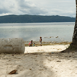 Papua kids playing on the white sandy beach.
