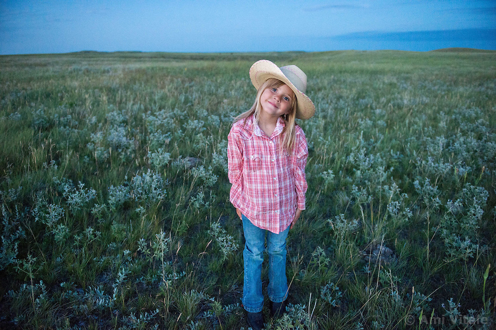 Layla Messerly, the daughter of Charlie Messerly helps her dad as he works on the Matador grass bank project with 13 ranching families in Eastern Montana  at the Matador ranch &quot;grass bank&quot;. The &ldquo;grass bank&quot; is an innovative way to leverage conservation gains, in which ranchers can graze their cattle at discounted rates on Conservancy land in exchange for improving conservation practices on their own &ldquo;home&rdquo; ranches. In 2002, the <br /> Conservancy began leasing parts of the ranch to neighboring ranchers who were suffering from  severe drought, offering the Matador&rsquo;s grass to neighboring ranches in exchange for their  participation in conservation efforts. The grassbank has helped keep ranchers from plowing up native grassland to farm it; helped remove obstacles to pronghorn antelope migration; improved habitat for the Greater Sage-Grouse and reduced the risk of Sage-Grouse colliding with fences; preserved prairie dog towns and prevented the spread of noxious weeds. (Photo By Ami Vitale)