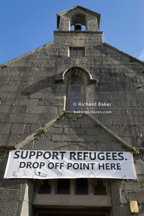 A banner showing where to drop-off items to help support refugees, on 13th September 2018, in Barmouth, Gwynedd, Wales.
