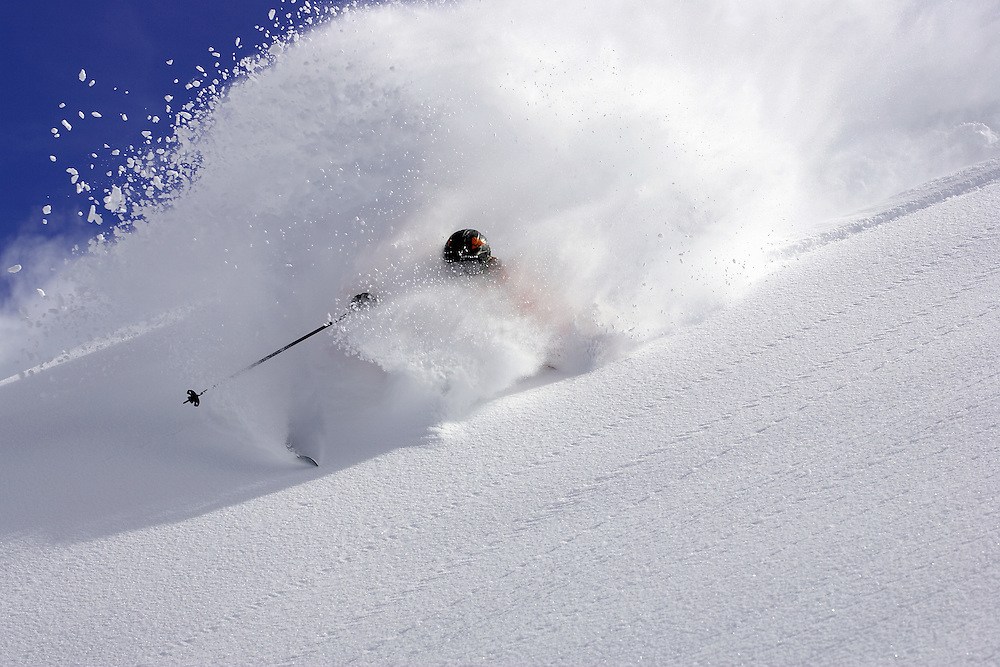 Male skier turning in fresh snow on steep mountainside, Serre Chevalier, France