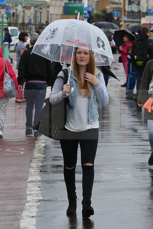 © Licensed to London News Pictures. 26/08/2014. Brighton, UK. A woman shelters under her umbrella when heavy rain hit Brighton during lunch time on Tuesday August 26th 2014. Temperatures are expected to reach around the 14C in Brighton and the South Coast. Photo credit : Hugo Michiels/LNP
