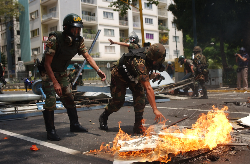 Members of the National Guard try to put out a street fire set by anti-government protestors  as riots continued in Caracas between the two groups. The country is awaiting a preliminary decision on the validity of signatures seeking a recall referendum.  It is expected that hundreds of thousands of signatures will have to go to a review process that the opposition will refuse to submit to.
