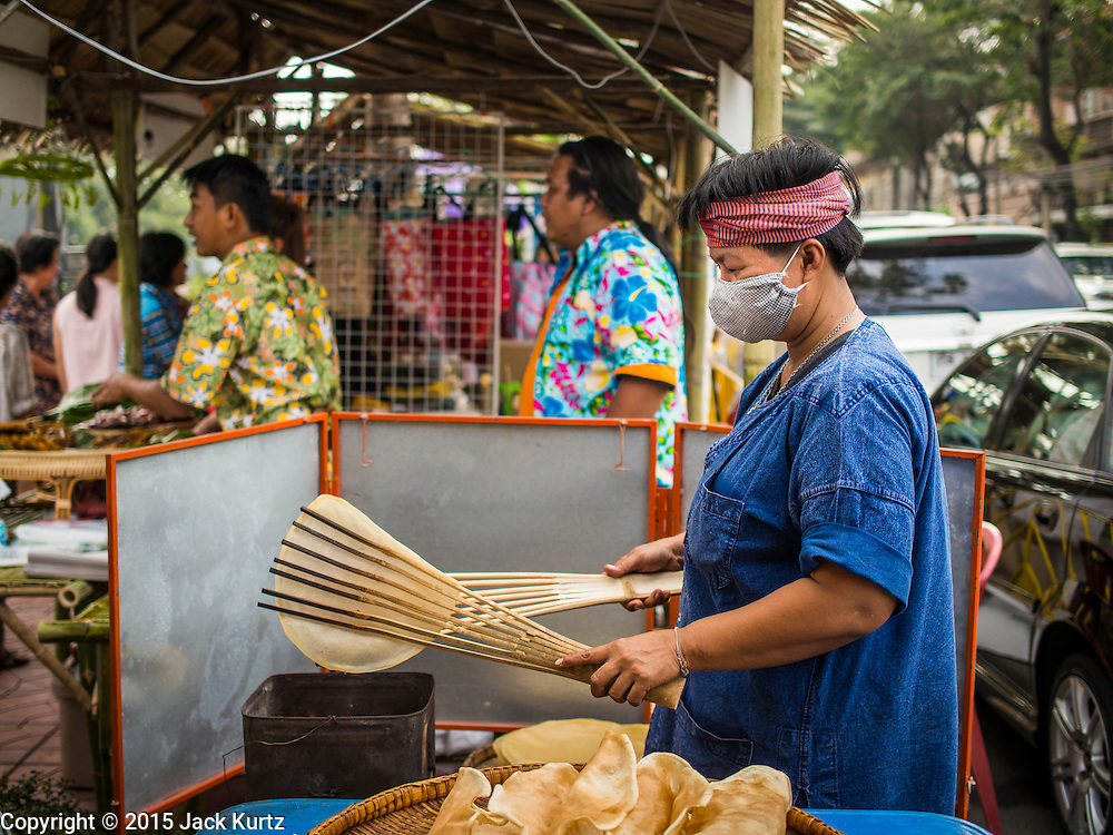 12 FEBRUARY 2015 - BANGKOK, THAILAND: A vendor makes grilled crackers in her stand on Khlong Phadung Krung Kasem, a 5.5 kilometre long canal dug as a moat around Bangkok in the 1850s. The floating market opened at the north end of the canal near Government House, which is the office of the Prime Minister. The floating market was the idea of Thai Prime Minister General Prayuth Chan-ocha. The market will be open until March 1.    PHOTO BY JACK KURTZ