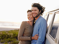 Young couple embracing by van parked by ocean half length