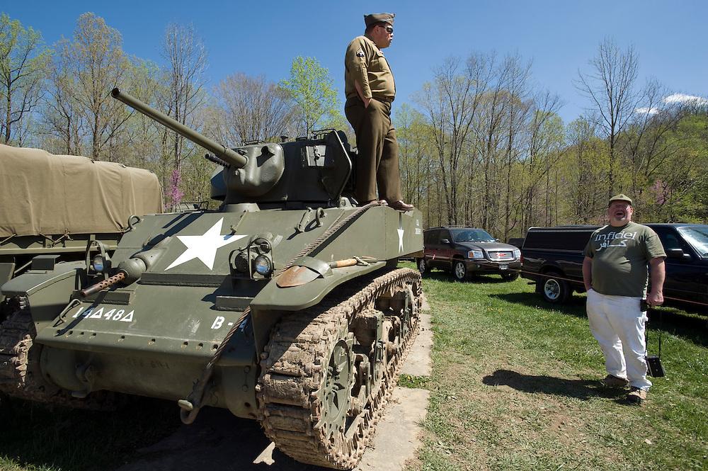 """Die Maschinengewehr und Waffen Show in Knob Creek, Luisville, Kentucky, USA, ist die groesste seiner Art in Nordamerika. An drei Schiessstaenden werden Waffen aller Art abgefeuert, vor allem Schnellfeuergewehre. Auch Kinder duerfen hier das Schiessen mit dem Maschinengewehr ueben. Im Angebot ist auch ein Jungle Walk, auf welchem je ein Teilnehmer mit einer Uzi auf im Wald versteckte Metallscheiben schiesst..Bid: Ein alter Panzer aus Privatbestand steht auf dem Parkplatz und ist fuer Besucher zugaenglich. Gepfleg wird er von (Name dem Autor bekannt), welcher sich mit einem Mann unterhaelt, welcher ein T-Shirt mit der Aufschrift """"Infidel"""" traegt"""