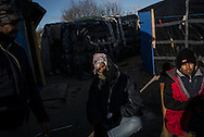 A group of Sudanese migrants try to warm up in the sun. Strong winds and low temperatures are whorstening the conditions of the migrants. Calais, France. FEDERICO SCOPPA/CAPTA