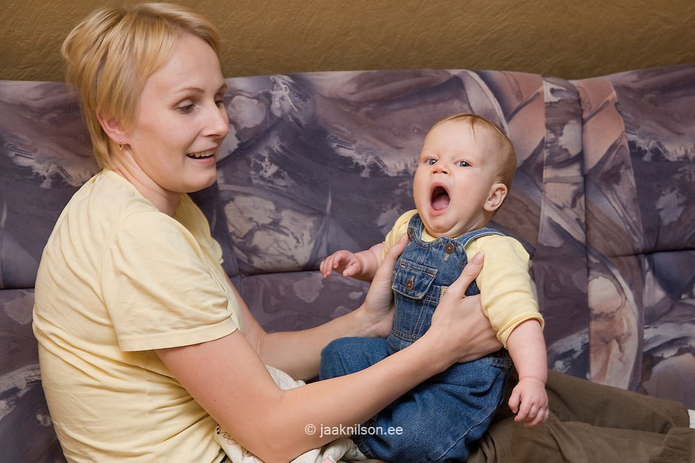 Young Happy Mother Sitting and Holding Yawning Infant Baby