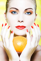 beautiful caucasian woman portrait holding a orange tangerine citrus fruit in studio on yellow background