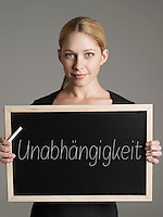 Portrait of young businesswoman holding blackboard with German text meaning Independence