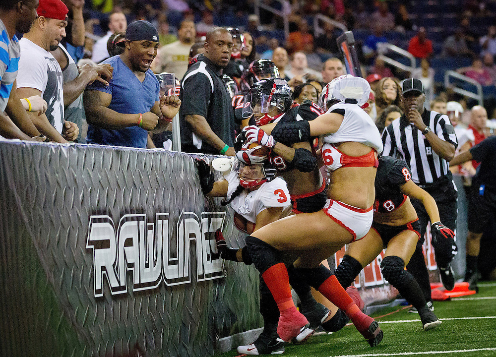 Much to the fans' delight, Jacqueline Smyth, and Morgan Anderson, at right, are slammed into the wall while tackling Atlanta Steam's Nasira Johnson during the first half of the Omaha Heart's 42-6 loss to the Atlanta Steam in Gwinnett, Ga., on Saturday, April 13, 2013. In arena football, the field is narrow and only 50 yards long. Fans pay extra to be seated along the wall, which is considered in bounds unless a player is tackled against it. <br /> <br /> ---<br /> <br /> The Lingerie Football League (now the Legends Football League) players say that they are athletes first. The lingerie is, in their minds, an unfortunate necessity. Many admitted that sex appeal was the reason fans attended the game, but talk to any woman who&rsquo;s played, and you&rsquo;ll learn that it&rsquo;s no powder puff or flag football. <br /> <br /> The players dedicate exhaustive effort, months of their time and thousands of dollars to a sport with little reward, to a league that takes more than it gives. Many players hope that one day the league won&rsquo;t be about the sex appeal but instead a showcase for female athleticism.<br /> <br /> &ldquo;People can get the impression it&rsquo;s just a bunch of bimbos out here,&rdquo; Omaha Heart quarterback Linsey Noble said. &ldquo;Everyone has their own story. You can&rsquo;t really judge people by the cover, by the book or the lingerie.&rdquo;<br /> <br /> <br /> Chicago Freelance Photographer | Alyssa Schukar | Photojournalist