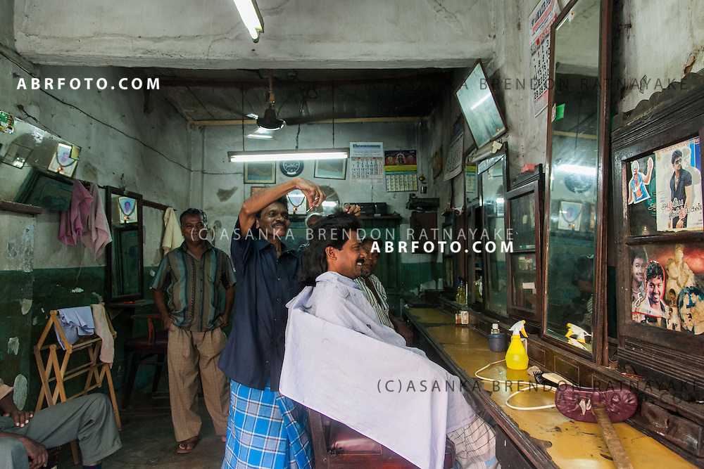 A man gets a haircut in a barber shop in Pettah, Colombo Sri Lanka. Asanka Brendon Ratnayake