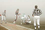 The fog rolls in as NFL side judge Dave Parry (64) and Chicago Bears cornerback Mike Richardson (27) look on after an unidentified Chicago Bears player gets tackled by Philadelphia Eagles wide receiver Cris Carter (80) after a pass interception during the 1988 NFL NFC Divisional playoff football game against the Philadelphia Eagles on Dec. 31, 1988 in Chicago. The Bears won the game 20-12. (©Paul Anthony Spinelli)
