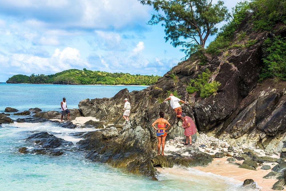 Yasawa-I-Rara, Fiji -- March 8, 2018. Tourists climb on the rocks of a beach in Yasawa-I-Rara in the Fiji Islands. Editorial Use Only.