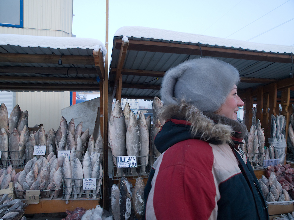 Verkaeuferin vor ihrem Stand mit tiefgefrorenen und stehenden Fischen auf dem Freiluft Markt im Zentrum von Jakutsk. Jakutsk hat 236.000 Einwohner (2005) und ist Hauptstadt der Teilrepublik Sacha (auch Jakutien genannt) im Foederationskreis Russisch-Fernost und liegt am Fluss Lena. Jakutsk ist im Winter eine der kaeltesten Grossstaedte weltweit mit durchschnittlichen Winter Temperaturen von -40.9 Grad Celsius. Die Stadt ist nicht weit entfernt von Oimjakon, dem Kaeltepol der bewohnten Gebiete der Erde.<br /> <br /> Seller in front of her stall with deep frozen and standing fishes on the Yakutsk outdoor fish market. Yakutsk is a city in the Russian Far East, located about 4 degrees (450 km) below the Arctic Circle. It is the capital of the Sakha (Yakutia) Republic (formerly the Yakut Autonomous Soviet Socialist Republic), Russia and a major port on the Lena River. Yakutsk is one of the coldest cities on earth, with winter temperatures averaging -40.9 degrees Celsius.