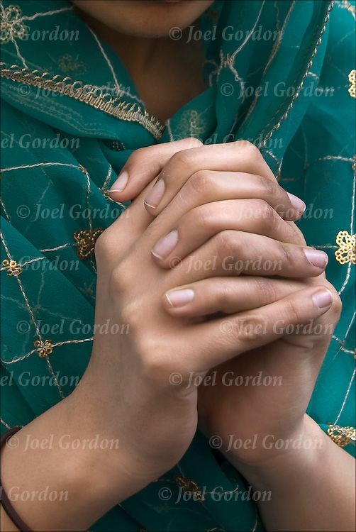 Close up of hands of Sikh-American young woman, wearing sari or saree praying before the start of the annual Sikh Day Parade in NYC.