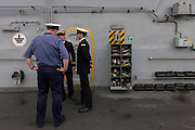 Student officers and a rating on duty on the top deck during a tour by the general public on-board the Royal Navy's aircraft carrier HMS Illustrious during a public open-day in Greenwich. Illustrious docked on the river Thames, allowing the tax-paying public to tour its decks before its forthcoming decommisioning. Navy personnel helped with the PR event over the May weekend, historically the home of Britain's naval fleet.