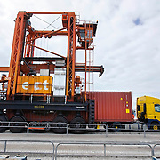 Nederland Zuid-Holland Rotterdam  27-08-2009 20090827 Foto: David Rozing .Serie over logistieke sector.ECT Delta terminal in de haven van Rotterdam. Telescopische spreader voertuigen vervoeren de containers op de terminal. Oppakken van een container   van een vrachtwagen voor verder transport. .ECT,European Container Terminals, at the Port of Rotterdam. Europe's biggest and most advanced container terminal operator, handling close to three- quarters of all containers passing through the Port of Rotterdam. ECT is a member of the Hutchison Port Holdings group (HPH), the world biggest container stevedore with terminals on every Continent. At the ECT Delta Terminal telescopic spreader vehicles transport the containers between ship and stack / trucks.  Terminal operations are highly automated for discharging and loading large volumes...Holland, The Netherlands, dutch, Pays Bas, Europe .Foto: David Rozing