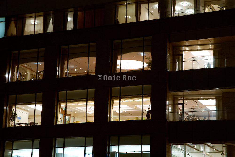 hotel and office building at night with one person standing in the window