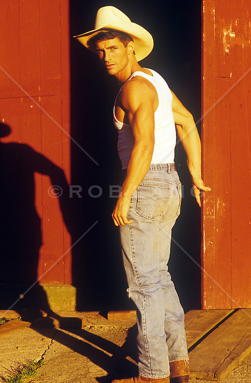 good looking cowboy about to enter a barn