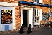 Obedient Labrador dogs wait outside Gurneys Fish Shop in Burnham Market in North Norfolk, UK