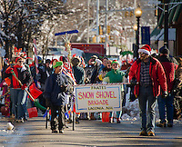 The Snow Shovel Brigade brings their sense of humor along with their shovels as they march down Main Street during the Holiday Parade on Saturday.  (Karen Bobotas/for the Laconia Daily Sun)