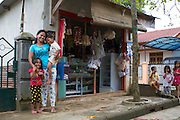 Jula Eha and her children outside her small shop on the front of her house in a quiet residential area near the town of Bogor, Indonesia.<br /> <br /> Her shop had mixed success at first and she used to become demotivated, but after subscribing to Usaha Wanita she regained her motivation and started to think of more creative ways to make her business a success. <br /> <br /> As a result her profits have increased and she is now saving money in an education fund for her children. <br /> <br /> She has also been able to follow Usaha Wanita's advice on savings and investments and she has joined a savings scheme and purchases new fridges and display cabinets for her store.