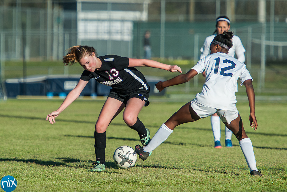 Hickory Ridge's Nia Gaither (12) and Jay M. Robinson's Marie Spokas (13) fight for the ball Friday night at Hickory Ridge High School in Harrisburg. The game ended in a 2-2 draw after double overtime.