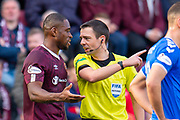 Referee Kevin Clancy speaks with Uche Ikpeazu (#19) of Heart of Midlothian FC during the Ladbrokes Scottish Premiership match between Heart of Midlothian and Rangers FC at Tynecastle Park, Edinburgh, Scotland on 20 October 2019.