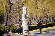 Elderly tourists look at statue of a high civil official, advisor to the emperor, on Spirit Way, Ming Tombs, Beijing, China