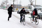 Twee fietsers rijden op de Amsterdamseweg in Arnhem door de sneeuw, terwijl een jongen zich haast om op tijd op het station te zijn.<br /> <br /> Tow cyclists are riding at the Amsterdamseweg in Arnhem in the snow, while a boy is running to be on time at the railway station.