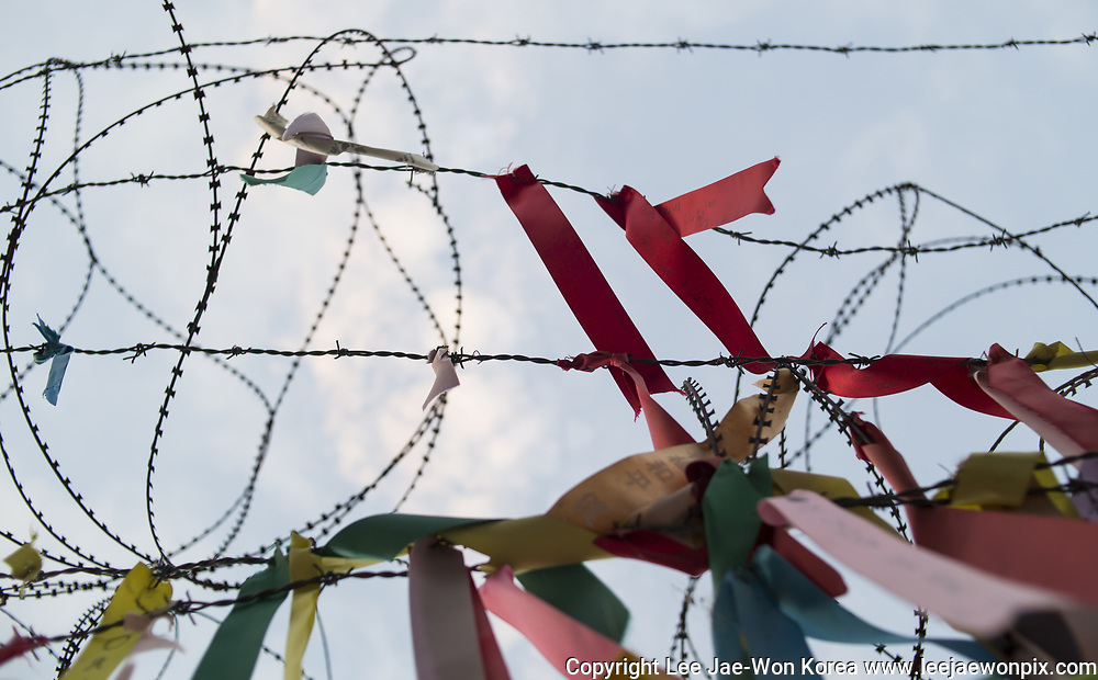 Ribbons on which people wrote their messages for the reunification of the two Koreas, are hung on the military fence at a village near the demilitarised zone separating the two Koreas in Paju, north of Seoul, South Korea, Aug 21, 2017. Photo by Lee Jae-Won (KOREA) www.leejaewonpix.com
