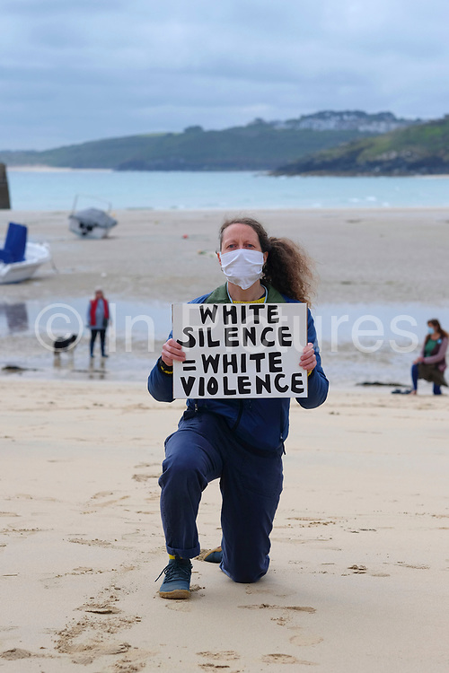 Climate change activists from Extinction Rebellion standing in solidarity with the world wide protest, Black Lives Matter following the death of George Floyd in the USA in their weekly protest called No Going Back which is usually linked to climate change and has now grown to become a national event, on Sunday at 10.00am on the 7th June 2020 in St Ives, United Kingdom. Black Lives Matter is an international human rights movement, originating from within the African-American community which campaigns against violence and systemic racism towards black people. Around 40 members of the St Ives community decided to protest by standing for an hour holding placards with slogans such as 'Black Lives Matter' and 'I can't breathe'. They walked through the town to the beach and harbour before taking the knee.