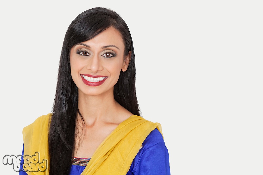 Portrait of an attractive Indian woman in traditional wear smiling against gray background