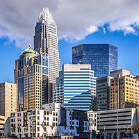 Charlotte downtown city buildings against a blue sky with clouds. Includes Bank of America Corporate Center, Bank of America Plaza, and 121 West Trade building. Charlotte, North Carolina is a major city in the Eastern United States of America