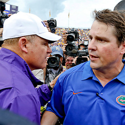 Oct 12, 2013; Baton Rouge, LA, USA; LSU Tigers head coach Les Miles shakes hands with Florida Gators head coach Will Muschamp following a game at Tiger Stadium. LSU defeated Florida 17-6. Mandatory Credit: Derick E. Hingle-USA TODAY Sports