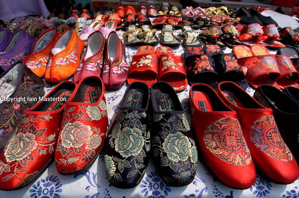 Many ornate embroidered traditional silk slippers for sale on stall in Beijing China